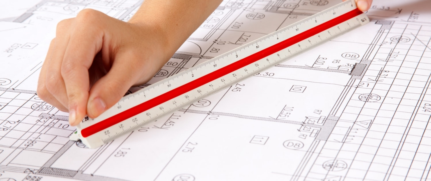 Two hands using a scale ruler on a set of blueprints Vancouver asbestos removal.