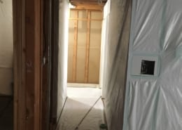 Asbestos abatement progress in Kitsilano home hallway